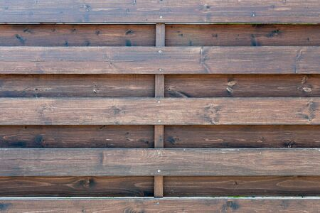 Old wooden texture painted with varnish. Fence or a fence of horizontal planks. Parallel slats of solid pine at intervals