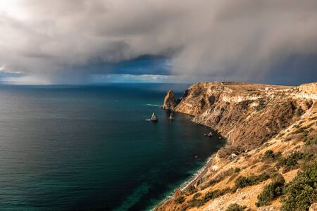 Rocky cliff against the stormy sky at the seashore. Landscape on the rocky shore of the Black Sea in Crimea. Storm approaching fog and gray skies with aquamarine waters along. Concept of nature force. Banque d'images