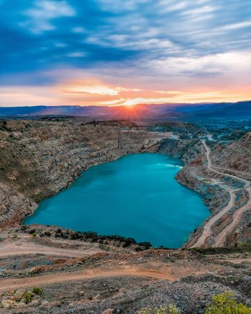 Sunrise over heart shaped blue quarry lake. Fluxing limestone Kadykovsky quarry, Balaklava, Crimea. One of the lowest points of Crimea is in Sevastopol, at the altitude of 14 meters below sea level.