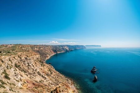 Panoramic seascape, calm azure sea and bright sun. View of the Black Sea coast in Crimea, Cape Fiolent in Sevastopol, Russia. Copy space. The concept of calmness, silence and unity with nature