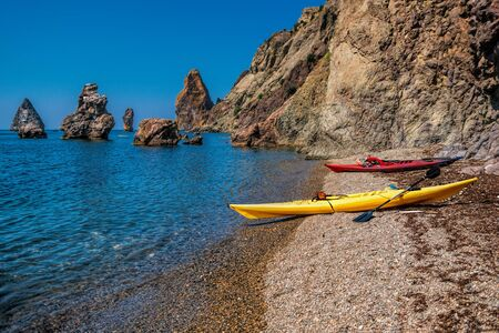 two kayaks on an isolated rocky beach, against the background of a cliff in the sea. Kayaking along the coast of the island near the rocks. The concept of an active life in harmony with nature. Foto de archivo