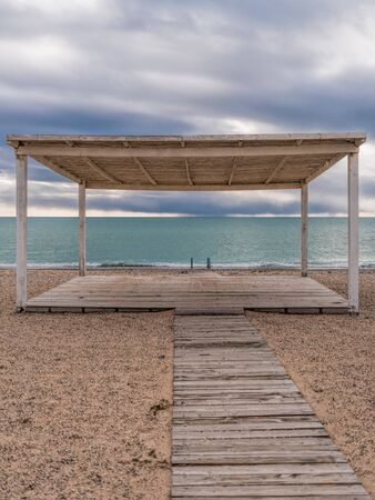 wooden walkway and sunshades on sand beach with azure sea, cloudy sky background. Empty beach with sunshades. Evpatoriya, Crimea. Copy space. The concept of calmness, silence and unity with nature. Stockfoto