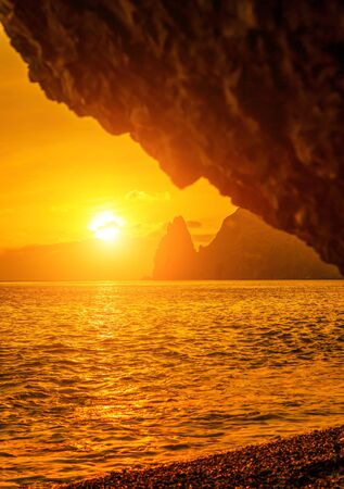 View of the sunset sea and the beach, the volcanic rock, sand and pebbles, volcanic basalt as in Iceland. Copy space. The concept of calmness, silence and unity with nature. Fiolent Sevastopol, Crimea