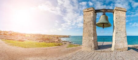 Big bronze bell on the sea shore in the ancient Greek city Chersonesus, Hersones in Sevastopol, Crimea. Copy space. Travel and relax concept. Imagens