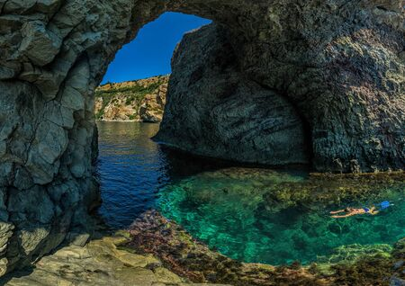 girl dive in the Dianas grotto Sevastopol. Fiolent, Crimea on a background of rocky shores. The concept of an travel, relax, active and healthy life in harmony with nature.