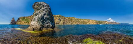 Yachts in the Sea on a background of rocky shores. Sea landscape with yachts and rocky coastline. The concept of an travel, relax, active and healthy life in harmony with nature. Cape Fiolent, Crimea