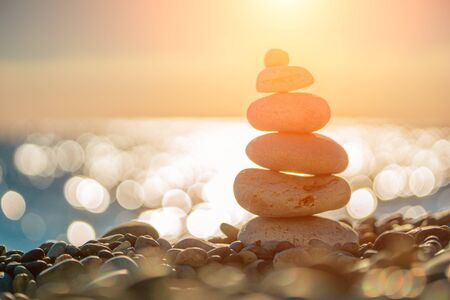 Balanced Pebbles Pyramid on the Beach on Sunny Day and Clear Sky at Sunset. Blue Sea on Background Selective focus, zen stones on sea beach, meditation, spa, harmony, calm, balance concept