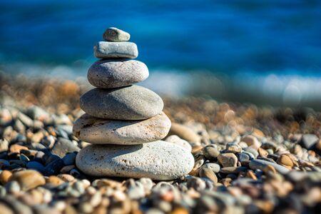 Balanced Pebbles Pyramid on the Beach on Sunny Day and Clear Sky at Sunset. Blue Sea on Background Selective focus, zen stones on sea beach, meditation, spa, harmony, calm, balance concept Stock Photo