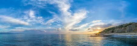 Beautiful colorful sunset above the azure sea with dramatic clouds. Panoramic view. Beauty world, nature and outdoors travel concept. Volcanic hills in the background. Imagens - 148096249