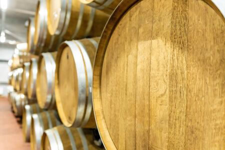 Selective focus. Row of Large French Oak Red Wine Barrels in a Modern Wine Warehouse Stock fotó