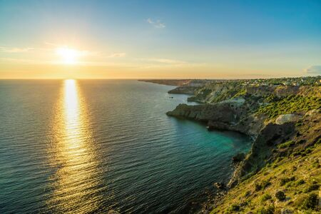 Panoramic seascape, view on rocky seashore, calm azure sea and bright sunset. Copy space. Copy space. Beauty world, nature and outdoors travel concept.