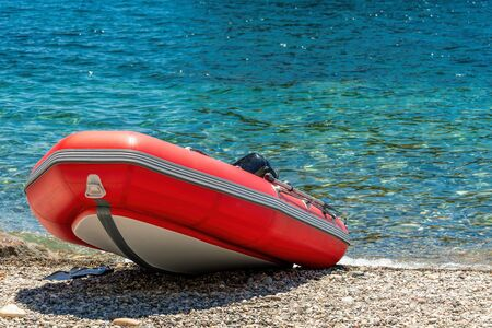 Red rescue inflatable boat, closeup. Empty marine rescue boat. Inflatable boat on the beach it is red in colour with a grey floor and black stripes