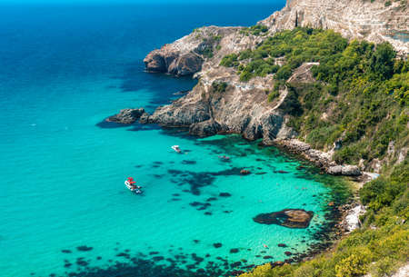 Boats and yachts in the crystal clear azure sea on a sunny day. The concept of an ideal place for summer travel and relaxation. Stok Fotoğraf
