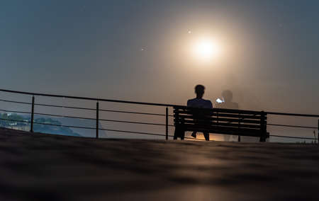 Silhouette of a loving couple on a bench in the park on the background of the moon and lunar path on water surface. Romantic evening on the sea under moonlight