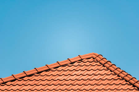 Brown tile roof under blue sky. The photo is divided on two part. One part is a roof made of clay tiles and the other is a blue sky. Brown surface of tile roof with natural color, texture and pattern