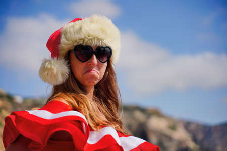 Young brunette woman in red swimsuit and Santa hat, swimming on kayak around basalt rocks like in Iceland. Back view. Christmas and travel concept