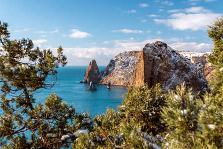 Snow covered rocky cliffs over sea. Winter sunset over the sea bay. Juniper tree under snow. Concept of winter holidays, travel, adventure and recreation Cape Fiolent in Balaklava, Sevastopol, Crimea.