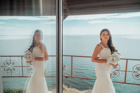 Gorgeous brunette bride posing with a bouquet on hotel terrace, looking at sea. Luxury destination, wedding makeup and hairstyle. Morning of the bride. Puffy lips and expressive eyes. Wedding concept