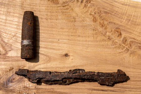 old rusty artillery shell and aircraft projectile on wooden background, shells bullets of world war 2 found, digged out from the ground