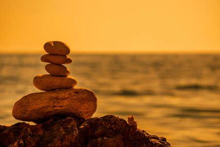 Pyramid stones on the seashore on a sunny day on the blue sea background. Happy holidays. Pebble beach, calm sea, travel destination. Concept of happy vacation on the sea, meditation, spa, calmness. Standard-Bild