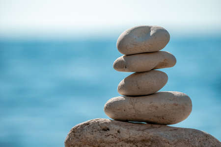 Pyramid stones on the seashore on a sunny day on the blue sea background. Happy holidays. Pebble beach, calm sea, travel destination. Concept of happy vacation on the sea, meditation, spa, calmness.