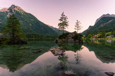Beautiful scene of trees on a rock island and mountains at sunset time in summer, Lake Hintersee National park Berchtesgadener Land, Upper Bavaria, Germany, Europe