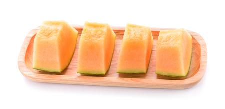 Melon in a wooden dish on a white background