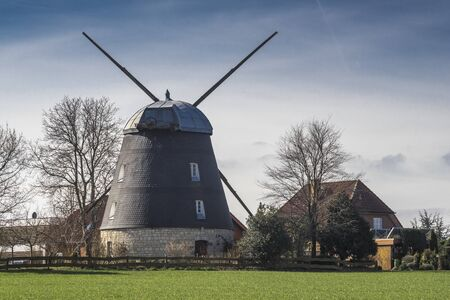 Old  windmill in Lower Saxony in Germany against cloudy sky Stok Fotoğraf