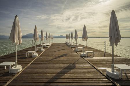 Wooden bridge and beach umbrellas Stok Fotoğraf