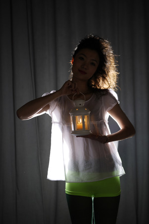 Portrait Of A Young Woman Holding Lamp In Spot Light