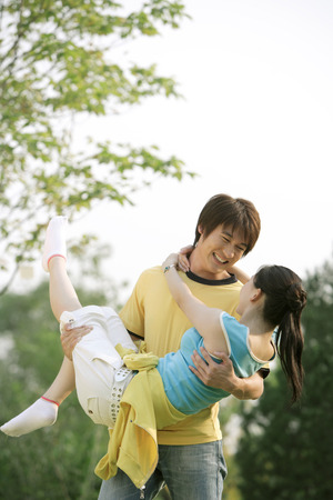 Young Man Lifting A Woman, Smiling