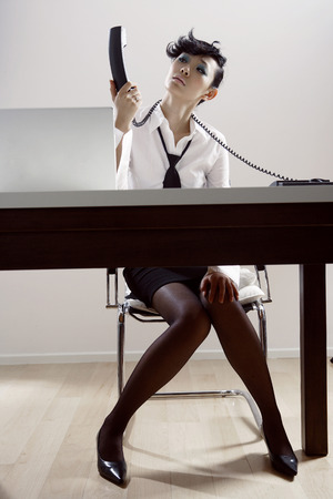 Businesswoman Looking At Telephone Receiver By Laptop LANG_EVOIMAGES
