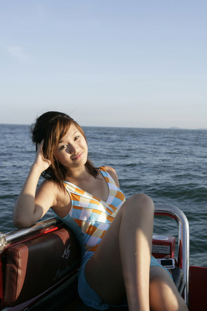 Young Woman Sitting In Boat, Smiling