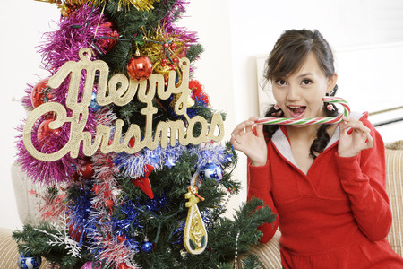 Portrait Of A Young Woman Sitting On Sofa With Candy Cane By Christmas Tree