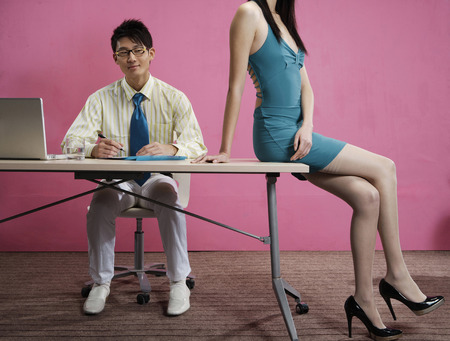 Office Young Man And Young Woman Sitting At Desk With Laptop
