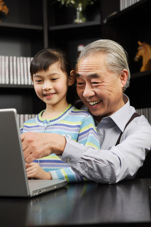 A Girl And Her Grandpa Playing The Computer