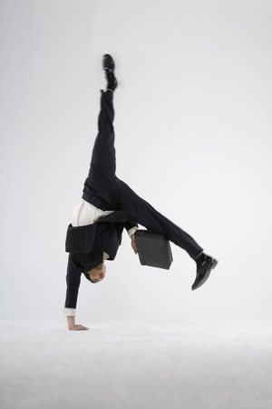 A Business Man Doing Handstand With One Hand LANG_EVOIMAGES