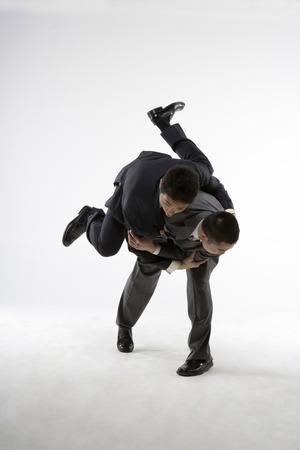 Two Business Men Wrestling LANG_EVOIMAGES