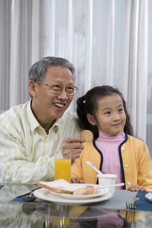 amabilidad: Una niña y su abuelo desayunando