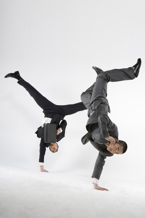 Two Business Men Doing Handstand With One Hand