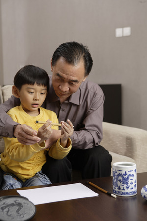 A Boy And His Grandpa Writing With Chinese Inkbrush LANG_EVOIMAGES