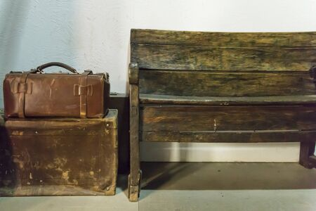 Old leather cases and an empty wooden bench