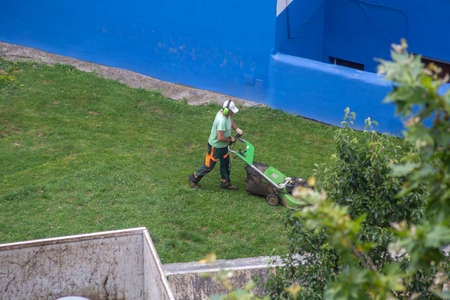 Male maintenance operator using a lawn mower