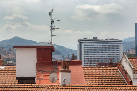 Rooftop with antennas, chimney and a satellite dish