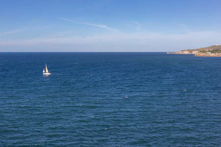 A boat sailing away from the coast