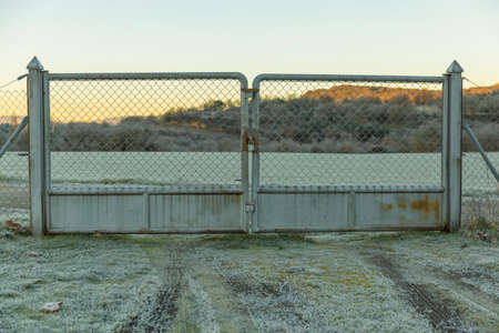An iron barrier closes the frosty field