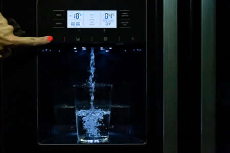 Filling a glass of water from a fridge