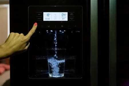 Filling a glass of water from a fridge dispenser