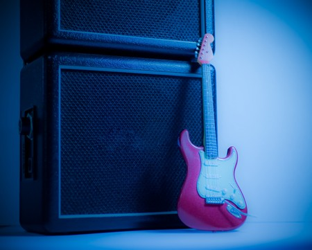 Red guitar model and the stack amplifier in blue light photo