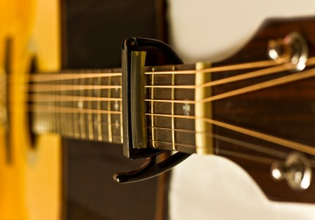 The capo on acustic guitar fingerboard Stock Photo - 7787015